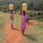 Unsere Köchin Sarah und unserer Kindergartnerin Eunice  holen das Wasser am Fluss.