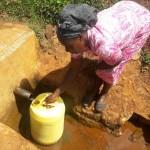 Sarah beim Flusswasser abfüllen