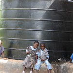 The children relax at the shadow of the watertank